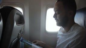 Ritratto del passeggero maschio, che sta leggendo la rivista negli aerei moderni video d archivio