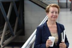 Ritratto del pendolare attraente della donna di affari maturi che sorride nel treno, nell'aeroporto o nella stazione della metrop Fotografia Stock Libera da Diritti