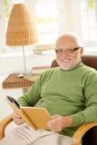 Ritratto del pensionato felice che si distende con il libro Immagine Stock