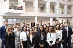 Ritratto del personale che sta nell'ingresso dell'ufficio moderno fotografia stock libera da diritti