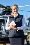 Ritratto del pilota femminile Standing In Front Of Helicopter With Di Immagini Stock