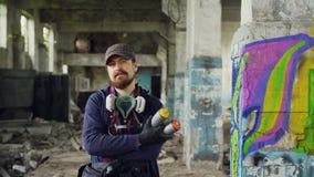 Ritratto del pittore barbuto dei graffiti del tipo che sta nella vecchia costruzione vuota con la pittura dei graffiti nel fondo  archivi video