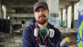 Ritratto del primo piano del cappuccio d'uso stante della costruzione abbandonato interno dell'uomo dell'artista barbuto bello de video d archivio