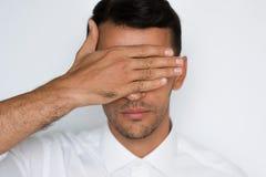 Ritratto del primo piano degli occhi bei della copertura dell'uomo con la mano isolata su fondo grigio Protezione bendata dell'uo fotografia stock libera da diritti