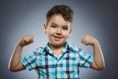 Ritratto del primo piano del bambino divertente Forte bambino che mostra i suoi muscoli del bicipite della mano fotografie stock libere da diritti