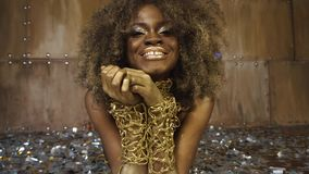 Ritratto del primo piano del modello femminile afroamericano sexy con trucco lucido dell'oro circondato da arte d'argento del fro archivi video