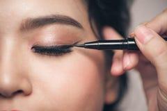 Ritratto del primo piano dell'eye-liner nero commovente della bella ragazza alla h Immagini Stock