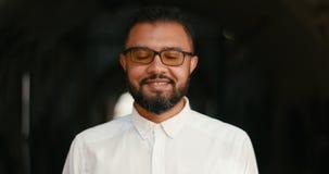 Ritratto del primo piano dell'uomo africano felice in occhiali che sorride felicemente alla macchina fotografica sopra fondo nero archivi video