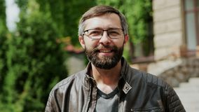 Ritratto del primo piano dell'uomo barbuto attraente che esamina la macchina fotografica e sorridere stock footage