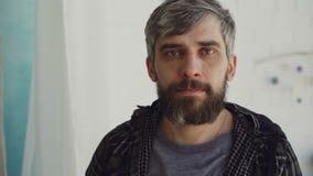 Ritratto del primo piano dell'uomo barbuto bello con gli occhi di marrone e l'abbigliamento casual d'uso dei capelli grigiastri e video d archivio