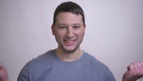 Ritratto del primo piano dell'uomo caucasico attraente adulto che è eccitato esaminando macchina fotografica con fondo isolato su video d archivio