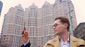 Ritratto del primo piano dell'uomo caucasico attraente che prende video della città sul telefono sui precedenti o sul livello urb stock footage