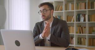 Ritratto del primo piano dell'uomo d'affari caucasico barbuto bello adulto in vetri che hanno una video chiamata sul computer por video d archivio