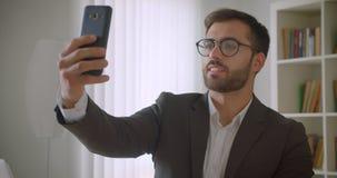 Ritratto del primo piano dell'uomo d'affari caucasico barbuto bello adulto in vetri che hanno una video chiamata sul telefono in stock footage