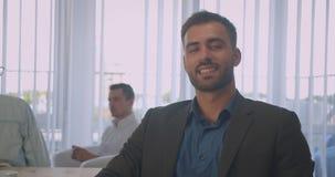 Ritratto del primo piano dell'uomo d'affari caucasico sicuro che esamina macchina fotografica che sorride allegramente nell'uffic video d archivio