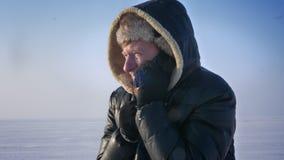 Ritratto del primo piano dell'uomo d'affari congelato in cappuccio che parla attivamente sul cellulare nel deserto della neve stock footage