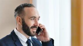 Ritratto del primo piano dell'uomo d'affari maschio sorridente attraente che parla facendo uso dello smartphone video d archivio