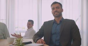 Ritratto del primo piano dell'uomo d'affari sicuro attraente che esamina macchina fotografica che sorride allegramente nell'uffic video d archivio