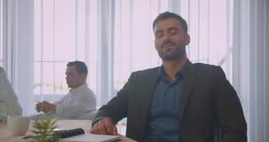 Ritratto del primo piano dell'uomo d'affari sicuro attraente che esamina macchina fotografica che sorride felicemente nell'uffici stock footage