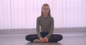 Ritratto del primo piano della ballerina professionista caucasica che si siede sul pavimento in studio leggero che guarda tranqui archivi video
