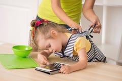 Ritratto del primo piano della bambina sveglia con la compressa Fotografie Stock