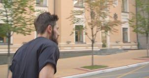Ritratto del primo piano della condizione maschio sportiva caucasica adulta del pareggiatore sulla via nella città urbana all'ape video d archivio