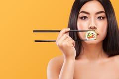 Ritratto del primo piano della donna asiatica che mangia i sushi ed i rotoli su un fondo giallo Copyspace immagine stock libera da diritti