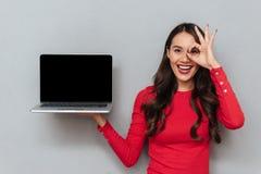 Ritratto del primo piano della donna attraente felice che mostra computer portatile vuoto Fotografia Stock Libera da Diritti
