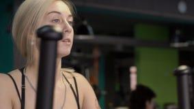 Ritratto del primo piano della donna che tiene gli sport che si preparano su un istruttore ellittico archivi video
