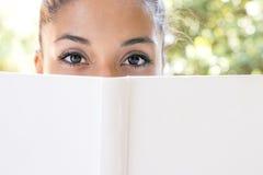 Ritratto del primo piano della donna con il libro bianco che esamina macchina fotografica immagini stock libere da diritti