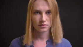 Ritratto del primo piano della donna convenzionale-vestita che alza i suoi occhi e che guarda seriamente nella macchina fotografi video d archivio