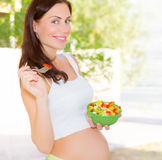 Donna incinta che mangia insalata Fotografie Stock