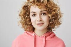 Ritratto del primo piano della donna riccio-dai capelli attraente d'avanguardia con il fronte sveglio che controlla fondo grigio  fotografia stock