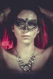 Ritratto del primo piano della donna sexy alla luce rossa del partito, maschera veneziana fotografia stock