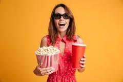 Ritratto del primo piano della donna uscita felice in vetri 3d che tengono il co Immagine Stock