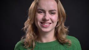 Ritratto del primo piano della femmina caucasica adulta che esamina macchina fotografica e che sorride allegramente archivi video