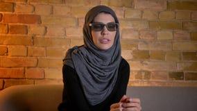 Ritratto del primo piano della femmina musulmana attraente adulta nel hijab che guarda un film 3D sulla TV mentre sedendosi sullo archivi video