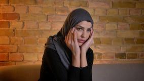 Ritratto del primo piano della femmina musulmana attraente adulta nel hijab che guarda un film horror sulla TV mentre sedendosi s video d archivio