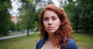 Ritratto del primo piano della giovane donna adorabile in parco con il fronte serio poi che sorride archivi video