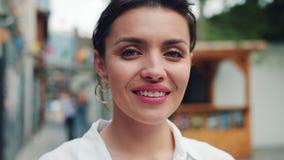 Ritratto del primo piano della giovane donna allegra che sorride esaminando macchina fotografica all'aperto stock footage