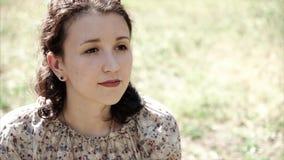 Ritratto del primo piano della giovane donna che si siede sull'erba Adolescente fantasticante soleggiato video d archivio