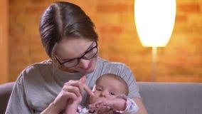 Ritratto del primo piano della madre che abbraccia con sua figlia neonata sveglia e che tocca il suo naso nel salone stock footage