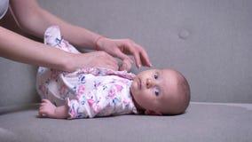 Ritratto del primo piano della madre che gioca con sua figlia neonata sveglia che si trova sul sofà nel salone stock footage