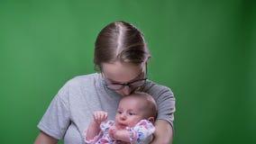 Ritratto del primo piano della madre graziosa che bacia sua figlia neonata gridante sveglia su fondo verde video d archivio