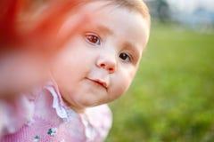 Ritratto del primo piano della neonata contro il prato verde che rispetta macchina fotografica all'aperto al sole Fotografia Stock