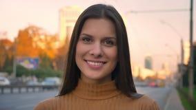 Ritratto del primo piano della ragazza castana attraente che si gira verso la macchina fotografica con il sorriso sincero sul fon stock footage