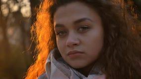 Ritratto del primo piano della ragazza caucasica abbastanza riccio-dai capelli che guarda attentamente e direttamente nella macch immagine stock