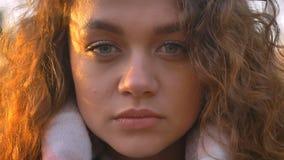 Ritratto del primo piano della ragazza caucasica abbastanza riccio-dai capelli che guarda seriamente nella macchina fotografica i immagine stock libera da diritti