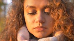 Ritratto del primo piano della ragazza caucasica abbastanza riccio-dai capelli che guarda tristemente verso il basso nel parco au immagine stock