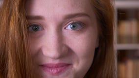 Ritratto del primo piano della studentessa caucasica della giovane testarossa allegra che esamina macchina fotografica che sorrid stock footage